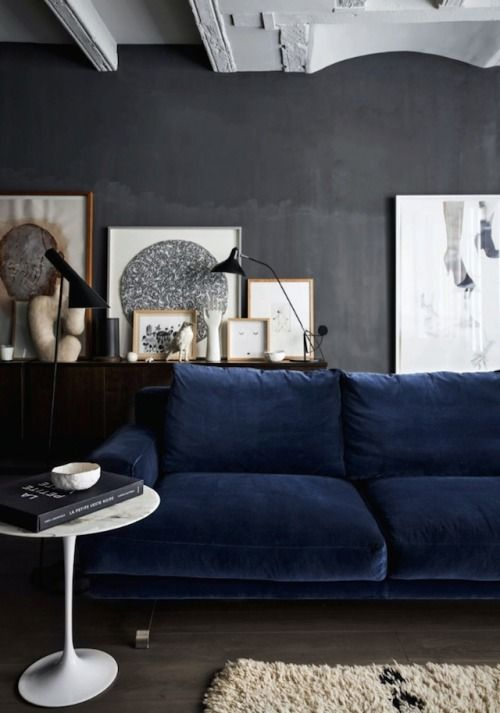 dark grey wall, dark floor, dark blue sofa, white accents; nice .